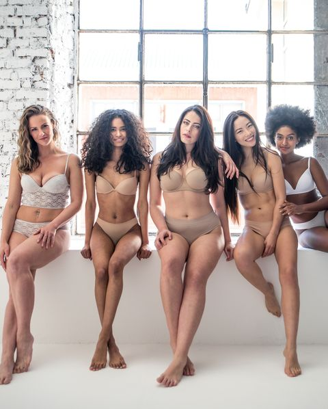 portrait of multi ethnic women in lingerie sitting on retaining wall