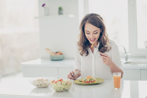 portrait of pretty, charming, stylish, joyful, cheerful woman in shirt eating fitness salad with knife and fork putting veggie in mouth keeping weight loss program, diet, healthy lifestyle