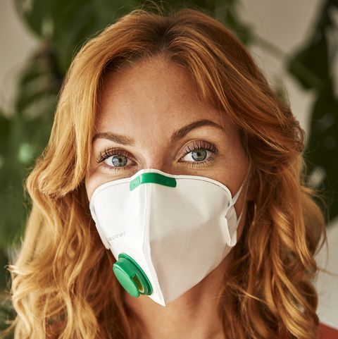 portrait of redhaired woman wearing a ffp2 mask at home