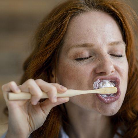 Portrait of redheaded woman brushing teeth