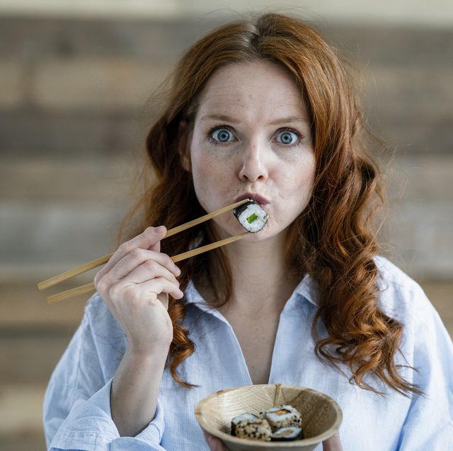 portrait of redheaded woman eating sushi