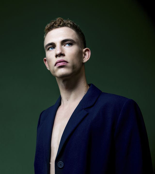 portrait of self confident young man wearing blue sports jacket in studio