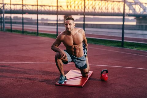 Portrait of shirtless muscular Caucasian man with serious face stretching leg while kneeling on the court. Next to him kettlebell.