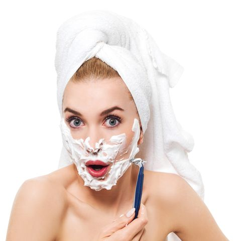 Portrait Of Shocked Young Woman Shaving Against White Background