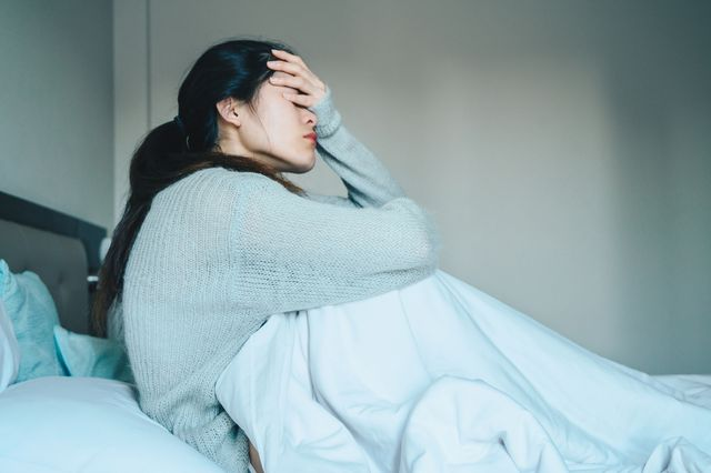 portrait of sickness woman sitting alone on the bed in the bedroom, self isolation herself during coronavirus pandemic outbreak