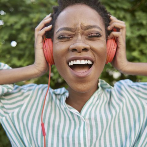 hobbies for women - Portrait of singing young woman with headphones