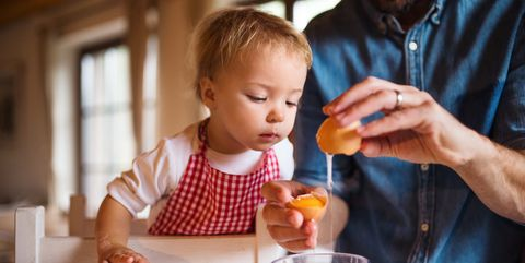 a portrait of small toddler girl in kitchen indoors, baking with father
