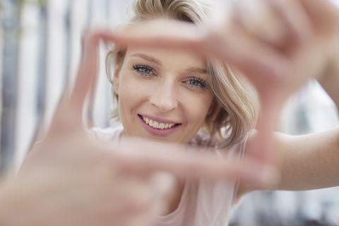 Portrait of smiling blond woman making a finger frame