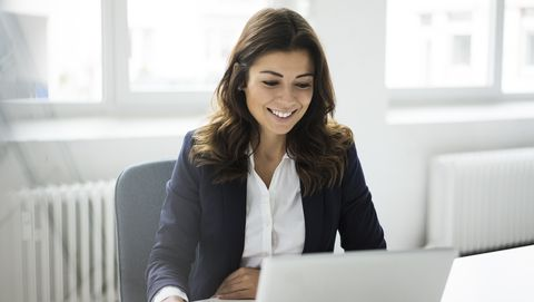 portrait of smiling businesswoman sitting at desk in the office working on laptop