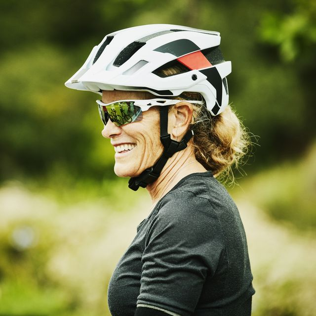 portrait of smiling mature woman relaxing after mountain bike ride with friends
