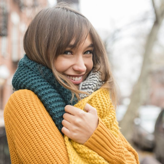 portrait of smiling mixed race woman wearing scarf in city
