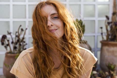 portrait of smiling redheaded young woman on terrace