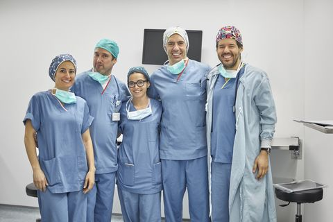 portrait of smiling surgeons standing in icu