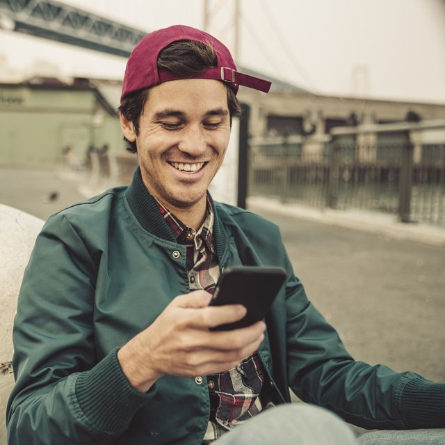 Portrait of smiling young man using cell phone
