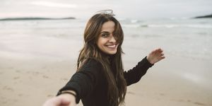 Portrait of smiling young woman holding hands on the beach