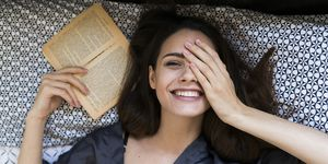 Portrait of smiling young woman lying on bed with a book covering one eye with her hand
