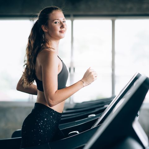Portrait Of Smiling Young Woman Running On Treadmill