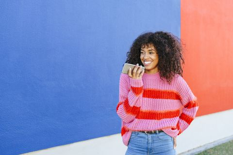 Portrait of smiling young woman sending a voice message with mobile phone