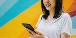 Portrait of smiling young woman using smartphone against colourful background in city