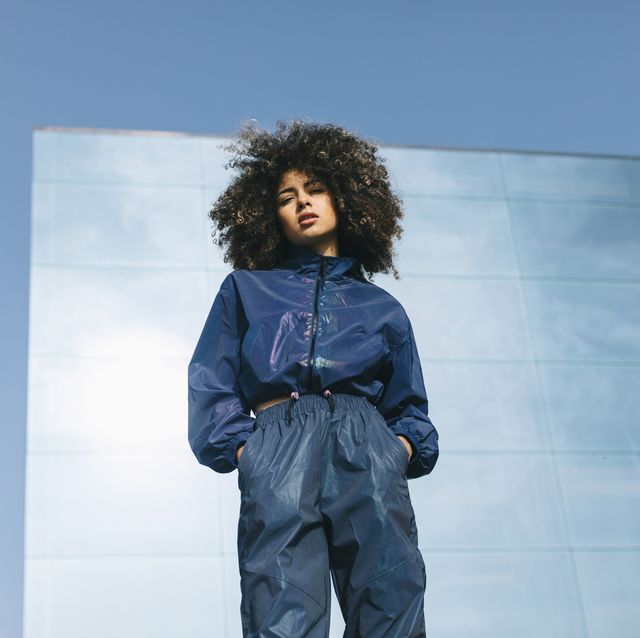 portrait of stylish young woman wearing tracksuit outdoors