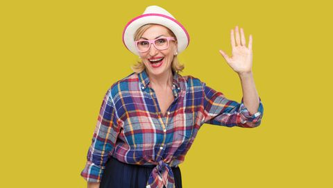 portrait of surprised modern stylish mature woman in casual style with hat and eyeglasses standing waving her hand and looking at camera with toothy smile