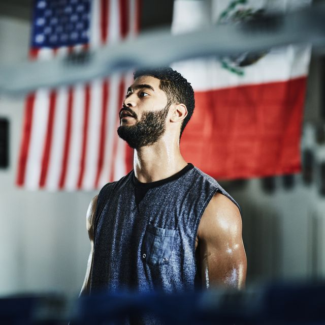 portrait of sweating male boxer listening to trainer during workout in boxing gym
