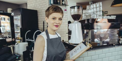 Portrait of waitress holding menu in a cafe