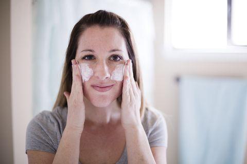 una chica se aplica crema en las mejillas