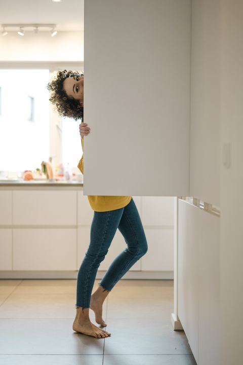 portrait of woman at the fridge in kitchen at home