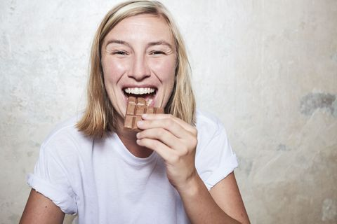 Portrait of woman eating bar of chocolate