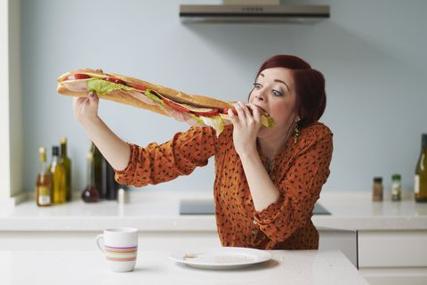 portrait of woman eating giant baguette