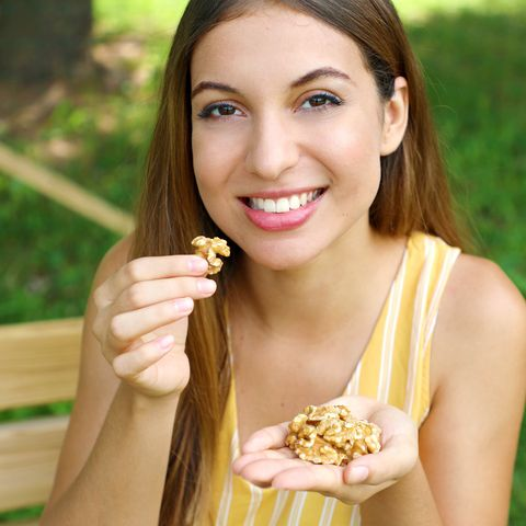 Portrait Of Woman Eating Walnuts While Sitting On Bench At Park