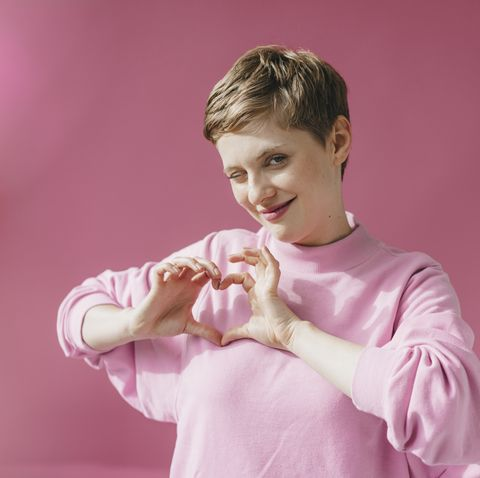 portrait of woman in pink twinkling shaping heart with her hands