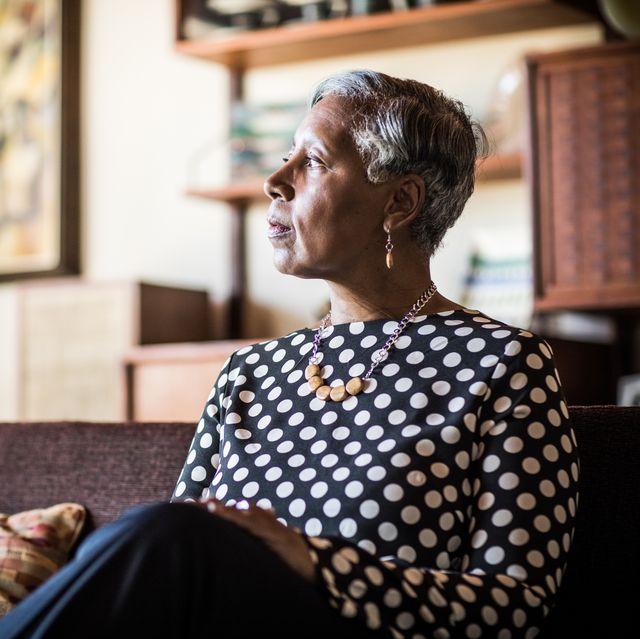 retrato de uma mulher de 60 anos sentada no sofá em casa