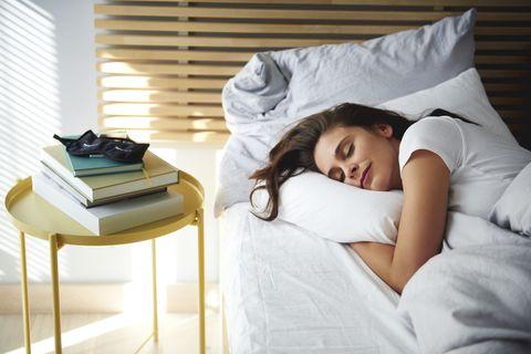 portrait of woman sleeping in bed by daylight