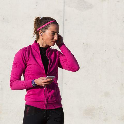 Portrait of woman wearing earphones holding smartphone