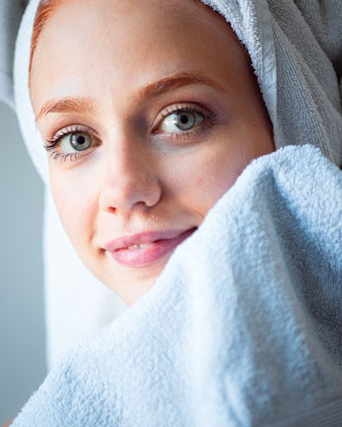 portrait of woman wiping cream on face with towel