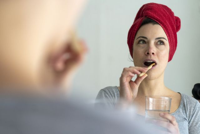 portrait of woman with head wrapped in a towel brushing heer teeth with wooden toothbrush