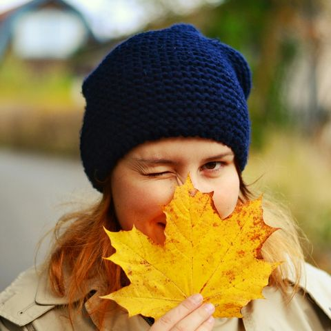 portrait of woman with maple leaf winking on street