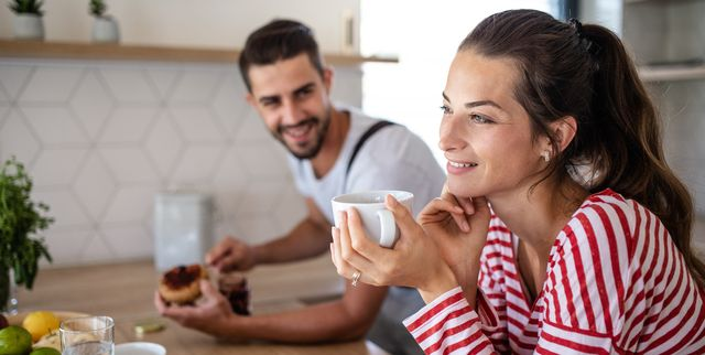 portrait of young affectionate cheerful couple preparing breakfast indoors at home