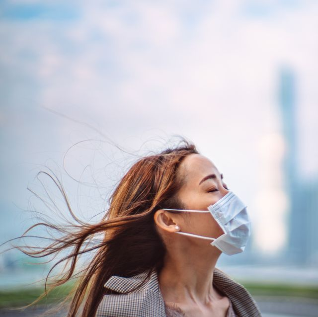 portrait of young asian lady with closed eyes wearing a face mask to protect and prevent from the spread of viruses in the city