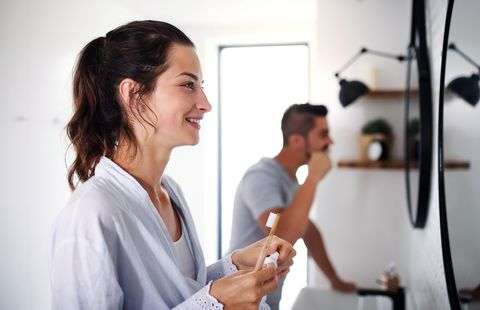 portrait of young couple standing indoors in bathroom at home, brushing teeth