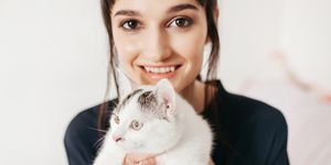 Portrait of young happy woman carrying cat
