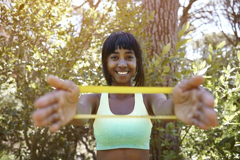 Portrait of young in rural setting, exercising using resistance band