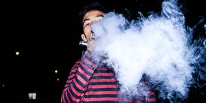 Portrait Of Young Man Smoking Electronic Cigarette At Night
