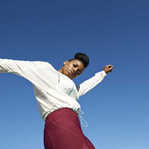 portrait of young sportswoman against clear blue sky