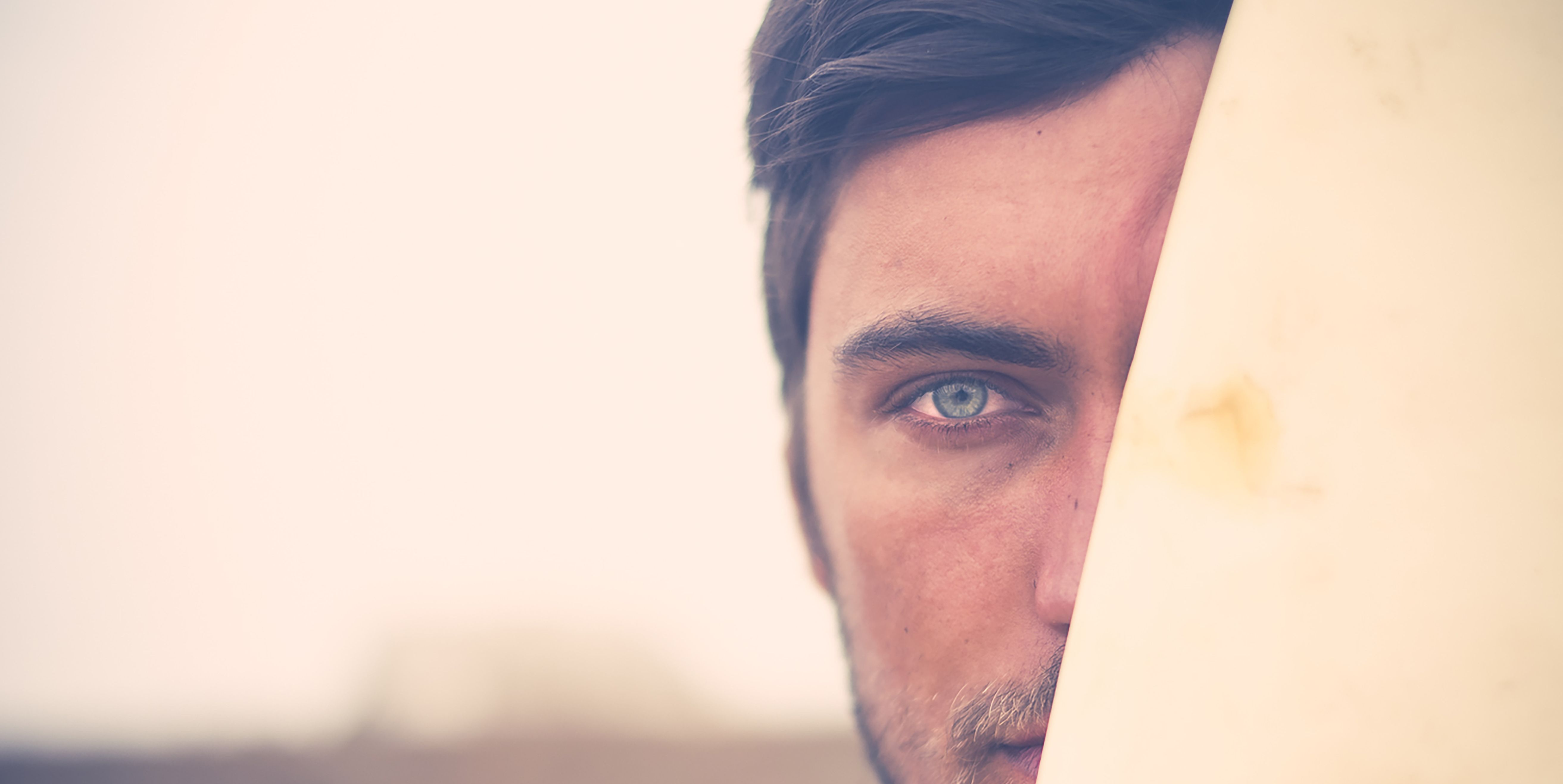 Portrait of young surfer hiding behind surfboard, close-up
