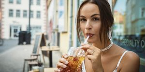 Portrait Of Young Woman Drinking Ice Tea From Glass At Restaurant