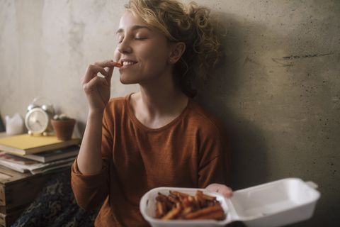 portrait of young woman eating french fries at home