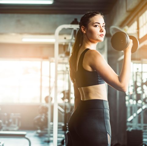 portrait of young woman exercising with dumbbells in gym
